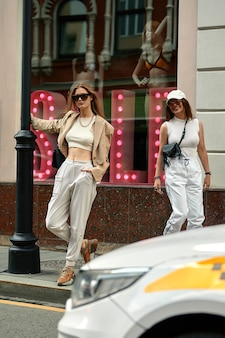 두 젊은 아름 다운 유행 소녀 거리에서 포즈. 세련된 선글라스와 밝은 색상의 옷을 입은 모델. 도시 생활. 여성 패션 개념.