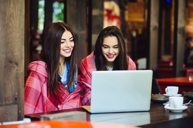 Two young and beautiful girl sitting at the table and looking for something on the internet