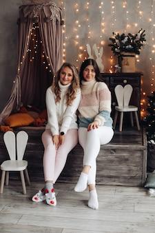 Due giovani belle amiche in abiti comodi si siedono accanto alla casa