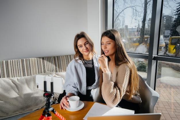 Две молодые красивые девушки сидят в кафе, записывают видеоблоги и общаются в социальных сетях.