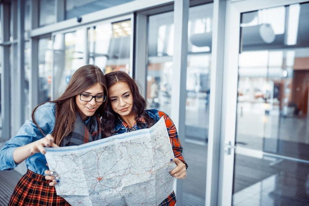 Two young beautiful girls are studying and looking at the map.