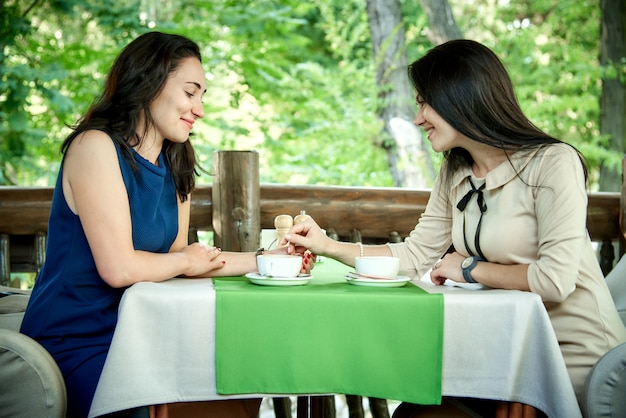 Two young beautiful girls chat in a cafe and drink coffee.