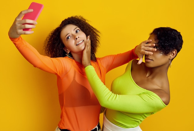 Two young beautiful girls in colorful clothes taking a selfie