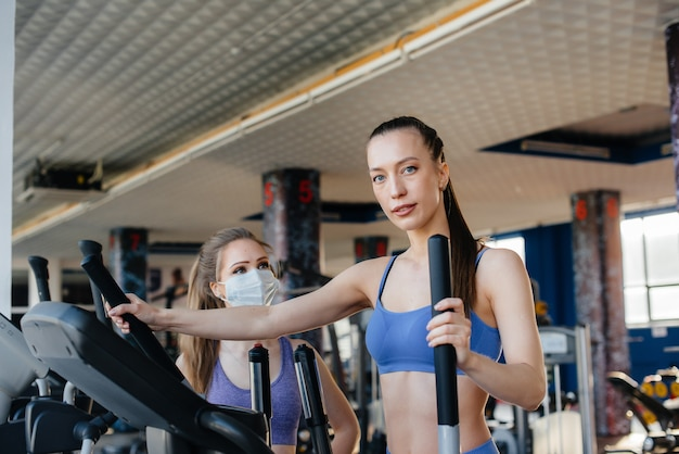 Two young beautiful girls exercise in the gym wearing masks during the pandemic