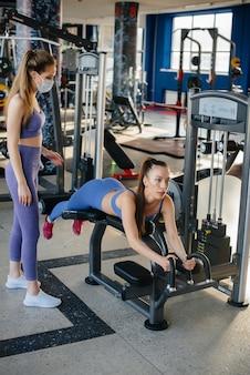 Две молодые красивые девушки тренируются в тренажерном зале в масках во время пандемии