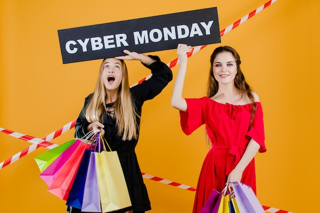 Two young beautiful girls have cyber monday sign with colorful shopping bags and signal tape isolated over yellow