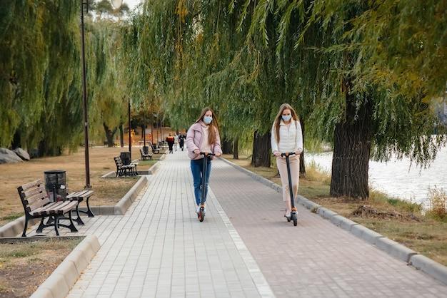 Две молодые красивые девушки в масках катаются на электросамокатах в парке теплым осенним днем. гулять в парке.