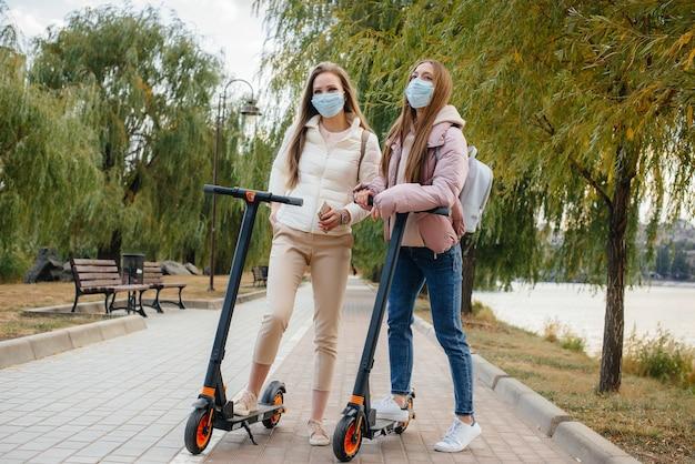 Две молодые красивые девушки в масках катаются на электросамокатах в парке теплым осенним днем. прогулка по парку.
