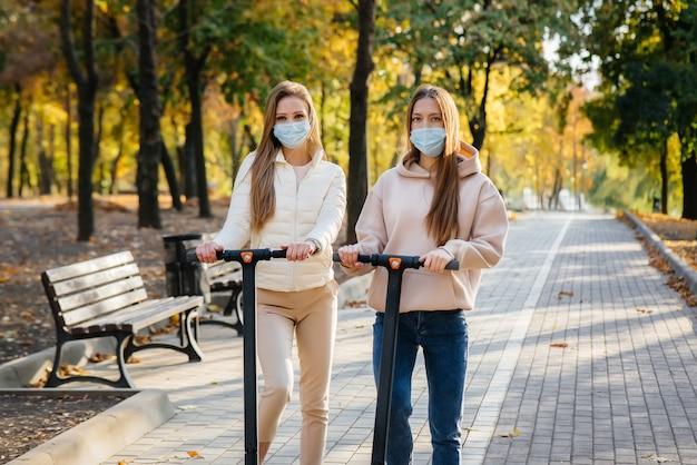 Две молодые красивые девушки в масках катаются на электросамокатах в парке теплым осенним днем.