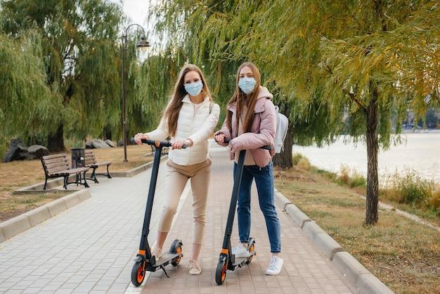 Две молодые красивые девушки в масках катаются на электросамокатах в парке в теплый осенний день