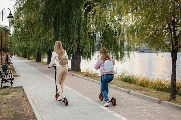 Две молодые красивые девушки в масках катаются на электросамокатах в парке теплым осенним днем