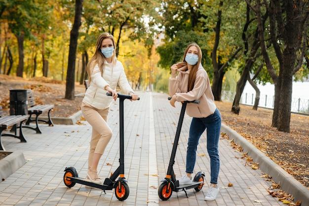 Две молодые красивые девушки в масках катаются на электросамокатах в парке