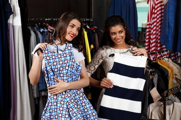Две молодые красивые девушки, делая покупки в торговом центре.