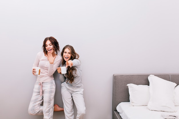 Two young beautiful girls in night pajamas with cups having fun  in sleeping room on grey wall . they look enjoyed and smiling.