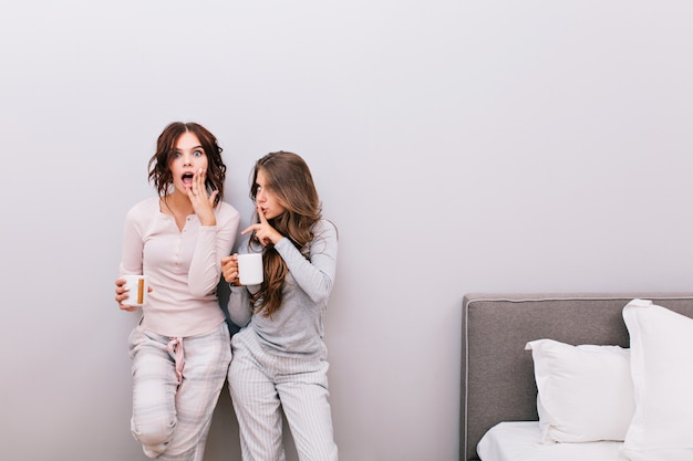 Two young beautiful girls in pajamas with cups having fun in sleeping room on grey wall . girl with curly hair looks astonished .