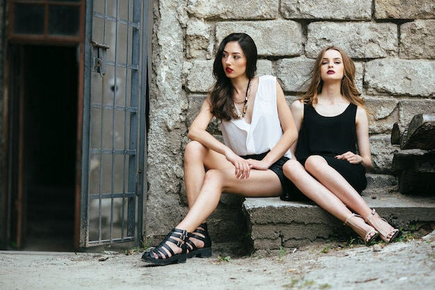 버려진 건물에 대해 포즈를 취하는 두 젊은 아름다운 소녀