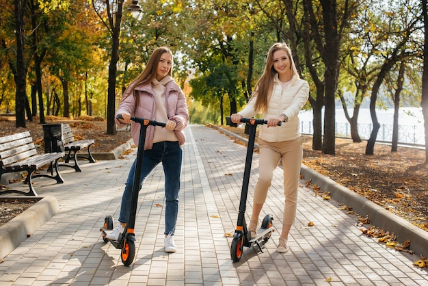 Две молодые красивые девушки катаются на электросамокатах в парке в теплый осенний день.