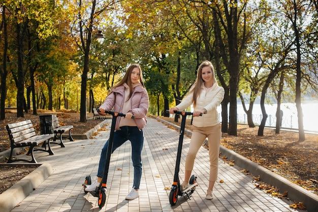 Две молодые красивые девушки катаются на электросамокатах в парке в теплый осенний день