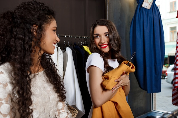 Two young beautiful girls shopping in mall.