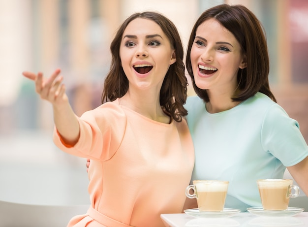 Two young beautiful girls sitting in urban cafe with coffee.