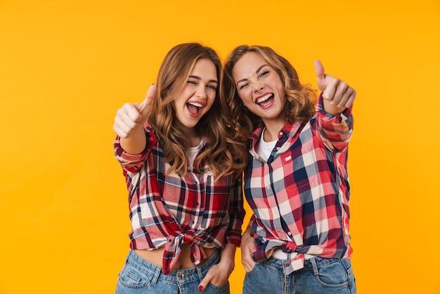 孤立した笑顔と親指を身振りで示す格子縞のシャツを着ている2人の若い美しい女の子