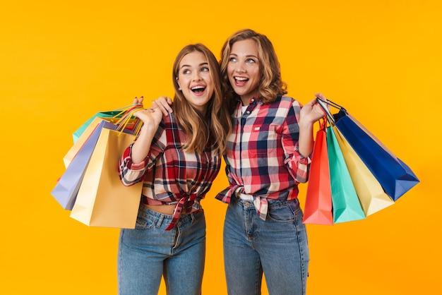 Две молодые красивые девушки в клетчатых рубашках улыбаются и держат красочные сумки для покупок