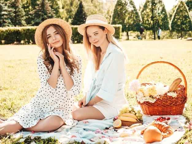 Две молодые красивые хипстерские девушки в модном летнем сарафане и шляпах. беззаботные женщины устраивают пикник на улице.