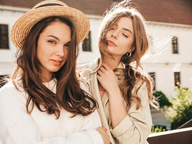 트렌디한 흰색 스웨터와 코트를 입은 두 명의 아름다운 힙스터 소녀