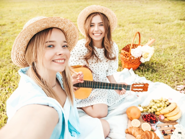 Two young beautiful hipster woman in trendy summer sundress and hats. carefree women making picnic outside.
