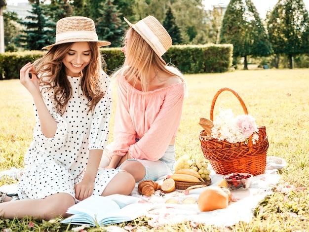 Due giovani bella donna hipster in prendisole e cappelli estivi alla moda. donne spensierate che fanno picnic all'esterno.