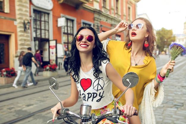 Due giovani belle donne pantaloni a vita bassa che guidano sulla strada della città di moto
