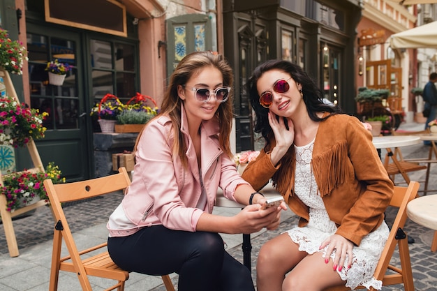 Due giovani belle donne hipster seduti al caffè
