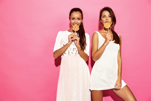 Two young beautiful hot smiling hipster women in trendy summer clothes. sexy carefree women posing near pink wall. positive models with lollipop