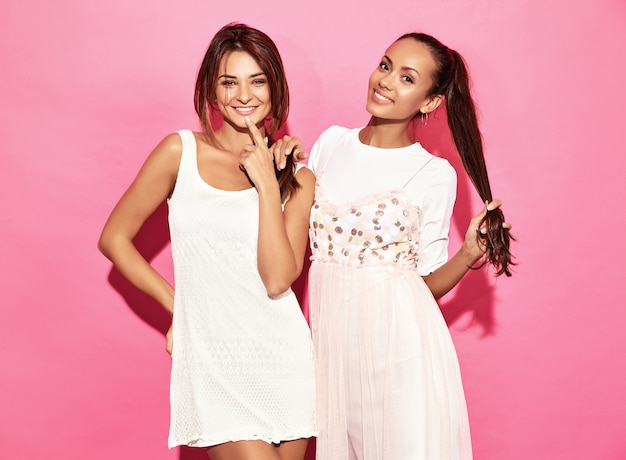 Two young beautiful hot smiling hipster women in trendy summer clothes. sexy carefree women posing near pink wall. positive models