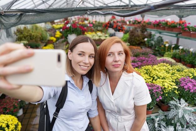 Due giovani belle donne che fanno selfie su sfondo di fiori nella serra