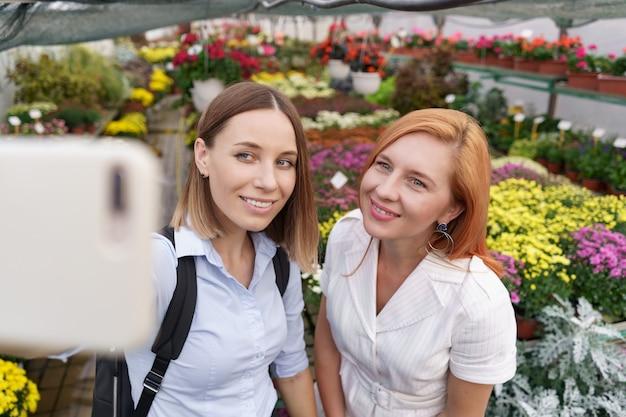 Две молодые красивые дамы делают селфи на фоне цветов в теплице