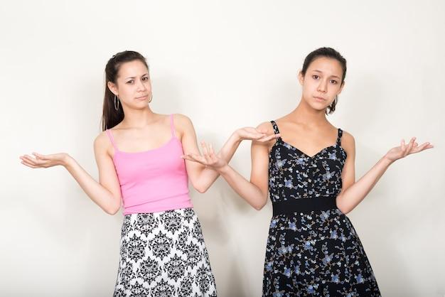 흰색에 함께 자매로 두 젊은 아름다운 다중 민족적인 여성