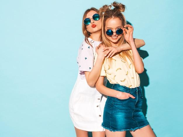 トレンディな夏のカラフルなtシャツの服の2人の若い美しい笑顔金髪流行に敏感な女の子。舌を見せて
