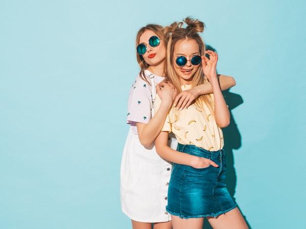 トレンディな夏のジーンズの2人の若い美しい笑顔金髪流行に敏感な女の子は服をスカートします。ハグ