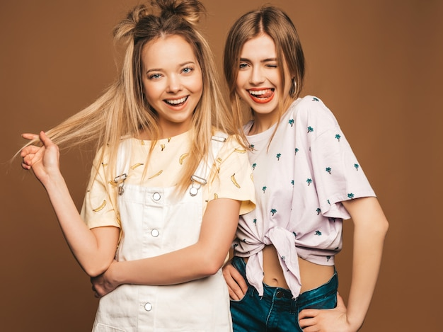 Two young beautiful smiling blond hipster girls in trendy summer colorful t-shirt clothes. sexy carefree women posing on beige background. positive models having fun