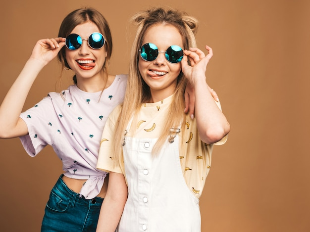 Two young beautiful smiling blond hipster girls in trendy summer colorful t-shirt clothes. sexy carefree women posing near beige wall in round sunglasses. positive models showing tongue