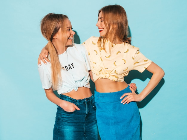 Two young beautiful smiling blond hipster girls in trendy summer colorful t-shirt clothes. sexy carefree women posing near blue wall. positive models looking at each other