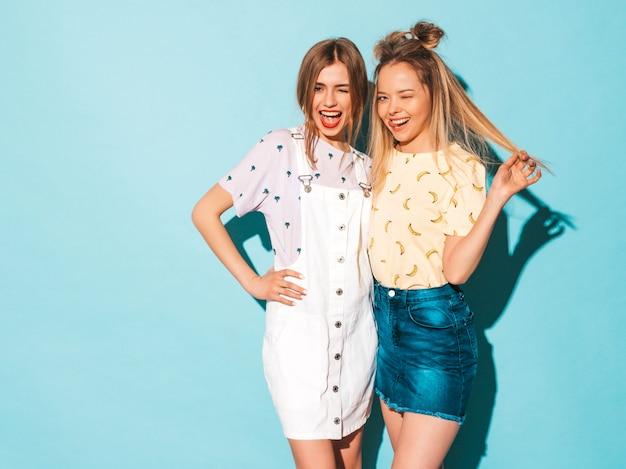 Due giovani belle ragazze bionde sorridenti dei pantaloni a vita bassa in vestiti variopinti della maglietta di estate alla moda. e mostrando lingua e ammiccanti