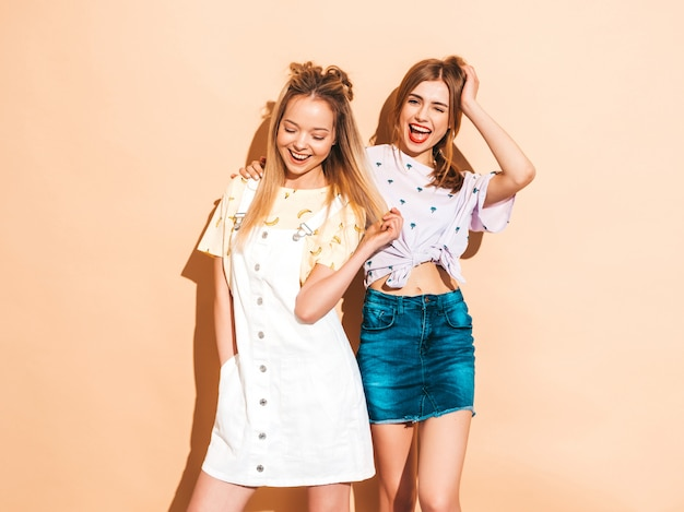 Two young beautiful smiling blond hipster girls in trendy summer colorful t-shirt clothes. and showing tongue