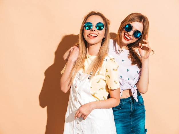Two young beautiful smiling blond hipster girls in trendy summer colorful t-shirt clothes.