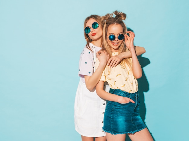 Two young beautiful smiling blond hipster girls in trendy summer jeans skirts clothes.  and hugging