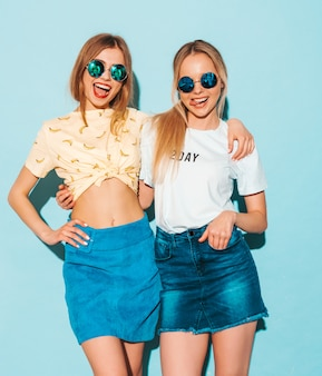 Two young beautiful smiling blond hipster girls in trendy summer jeans skirts clothes.  and showing peace sign