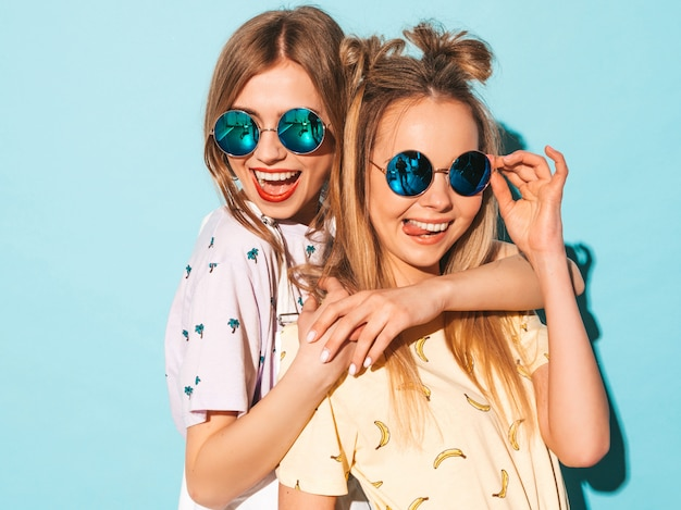 Two young beautiful smiling blond hipster girls in trendy summer jeans skirts clothes.  and showing tongue