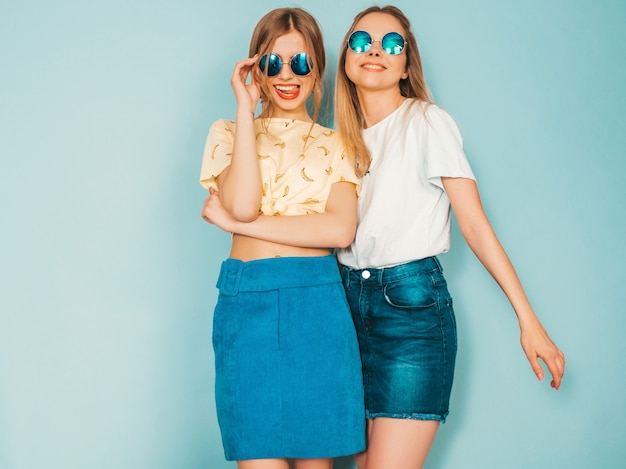 Two young beautiful smiling blond hipster girls in trendy summer jeans skirts clothes.
