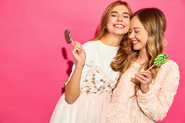 Two young beautiful smiling blond hipster women in trendy summer clothes. carefree hot women posing near pink wall. positive funny models hugging with lollipop